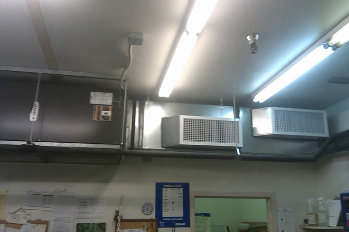 Simple commercial laundry cooling system, horizontal installation with exposed ductwork.