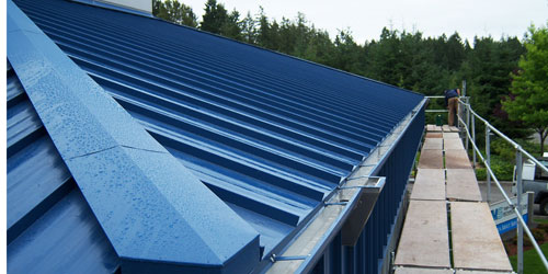 Commercial roof retrofits with roof gutters, leader heads and hidden fasteners.